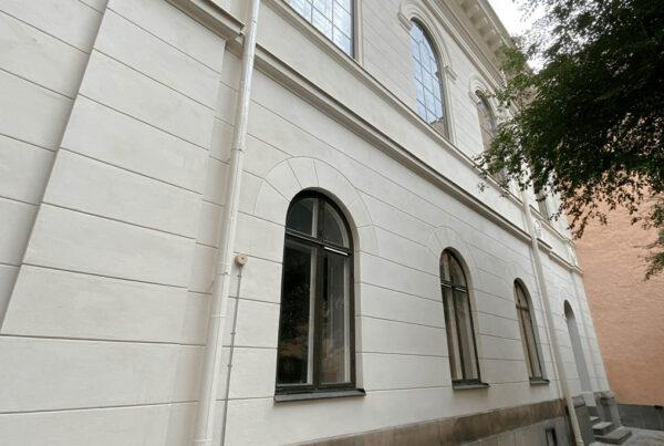 Vit fasad med gröna fönster
